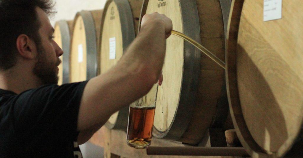 enchendo a garrafa do barril de cachaça